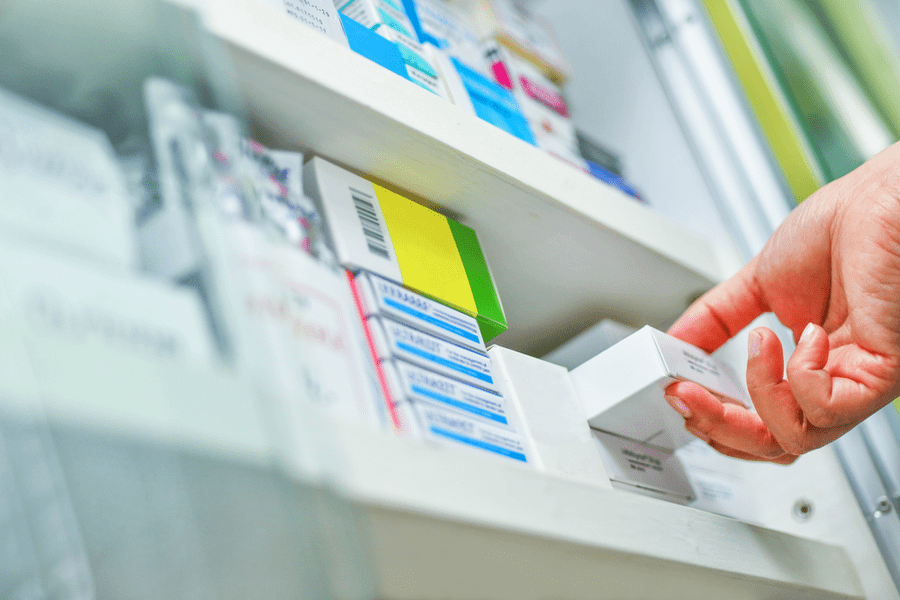 Close up of hand at pharmacy grabbing prescription from shelf